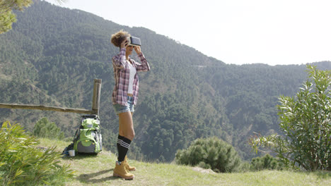 Young-woman-in-VR-glasses-among-mountains
