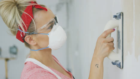 Woman-polishing-wall-with-sandpaper-