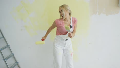 Relaxed-woman-dancing-with-paint-roller