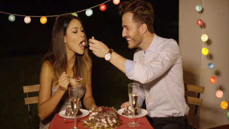 Loving-young-man-feeding-his-girlfriend-cake