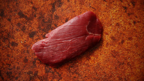 Piece-of-raw-fresh-beef-steak-placed-on-rusty-background
