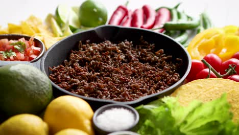 Ingredients-for-Chili-con-carne-in-frying-iron-pan-on-white-wooden-table