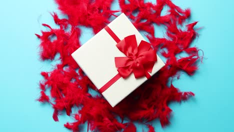 Box-with-a-gift-tied-with-a-ribbon-placed-on-red-feathers