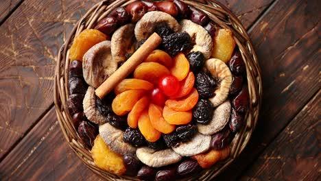 Mischung-Aus-Getrockneten-Früchten-In-Einem-Kleinen-Weidenkorb-Auf-Holztisch
