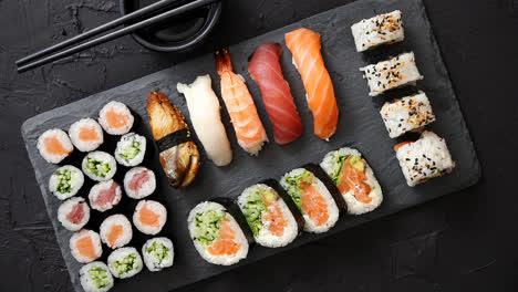Rollos-De-Sushi-Con-Salmón-Y-Atún-Servidos-En-Una-Placa-De-Piedra-Negra