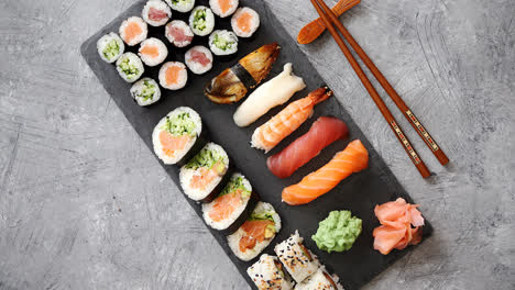 Composition-of-different-kinds-of-sushi-rolls-placed-on-black-stone-board