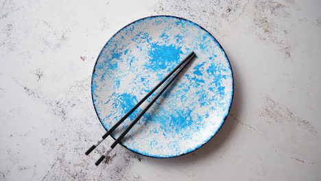Blue-hand-painted-ceramic-serving-plate-with-wooden-chopsticks-on-side