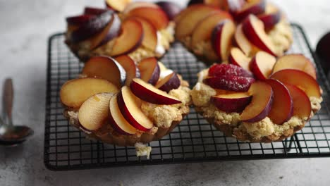 Homemade-crumble-tarts-with-fresh-plum-slices-placed-on-iron-baking-grill