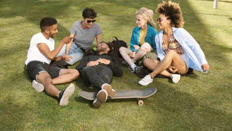 Lounging-friends-on-meadow-in-park-