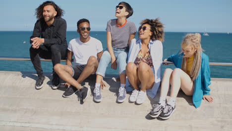 Trendy-young-friends-chilling-on-seafront-