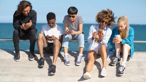 Young-diverse-people-with-mobile-phones-on-seafront-