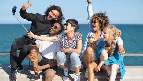 Laughing-friends-taking-selfie-on-seafront-
