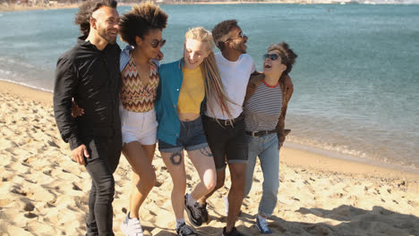 Trendy-young-friends-strolling-on-beach-
