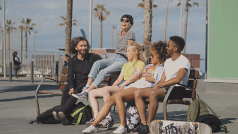 Trendy-young-friends-on-bench-on-street