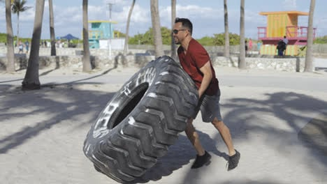 Man-working-out-with-tyre