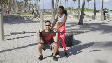 Woman-helping-man-with-workout-on-beach