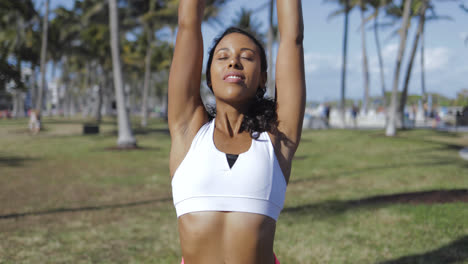 Relaxing-black-woman-training-in-sunny-park