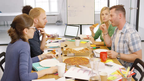 Young-people-enjoying-pizza-in-office