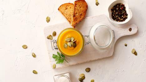 Pumpkin-soup-in-glass-jar-on-cutting-board