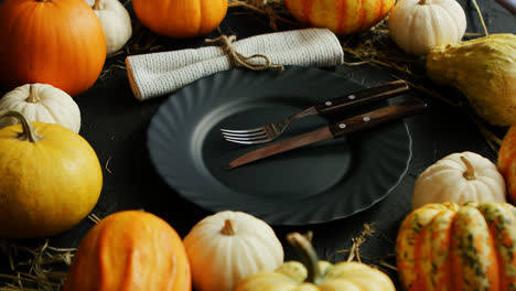 Black-plate-and-cutlery-surrounded-by-pumpkins