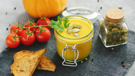 Creamy-pumpkin-soup-in-jar-with-bread-and-tomatoes