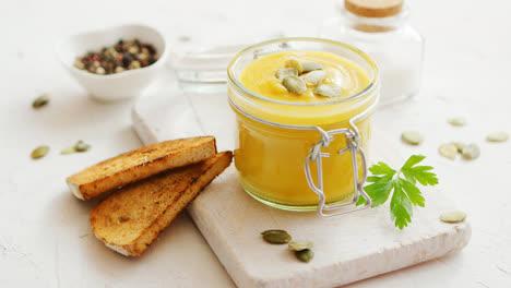 Pumpkin-soup-in-glass-jar-with-bread