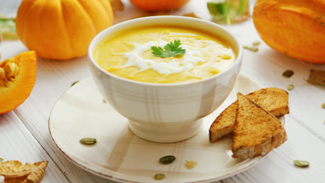 Pumpkin-soup-in-bowl-served-with-bread