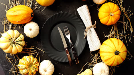 Black-plate-surrounded-by-yellow-pumpkins