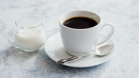 Cup-of-coffee-and-pitcher-of-milk