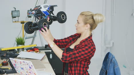 Woman-examining-radio-controlled-car-in-workshop