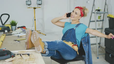Relaxed-female-at-workbench-talking-on-smartphone-