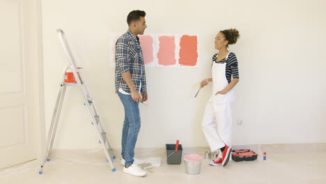 Young-couple-trying-to-decide-on-a-paint-color