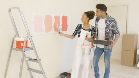Young-couple-discussing-shades-of-paint-color