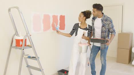 Joven-Pareja-Discutiendo-Tonos-De-Color-De-Pintura