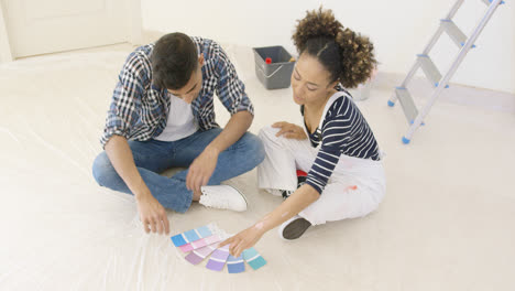 Couple-looking-at-paint-swatches-for-decorating