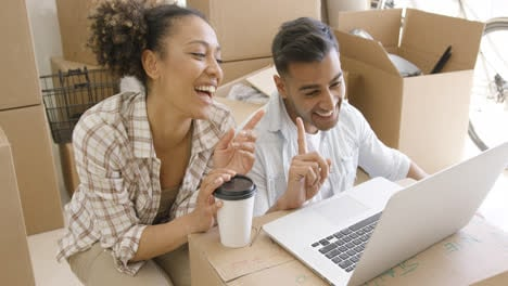 Happy-mixed-race-couple-discuss-while-using-laptop