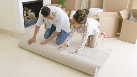 Young-couple-rolling-up-a-rug-as-they-move-house