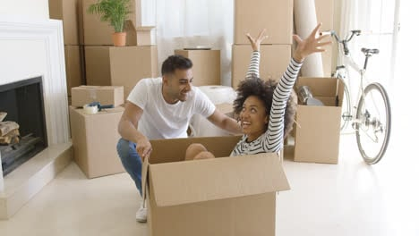Happy-mixed-race-couple-having-fun-break-with-unpacking