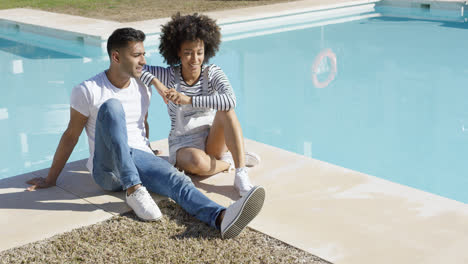 Young-woman-relaxing-with-her-boyfriend-poolside