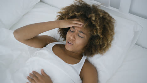Young-woman-having-headache-lying-in-bed