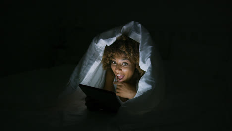 Excited-woman-under-blanket-with-tablet