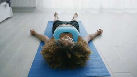 Woman-lying-on-mat-relaxing-and-breathing