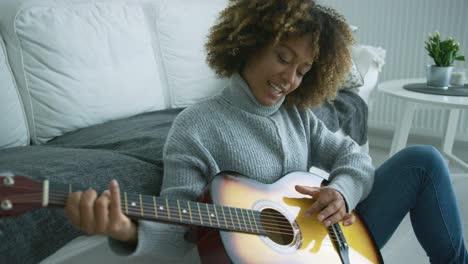 Mujer-Joven-Tocando-La-Guitarra-En-Casa
