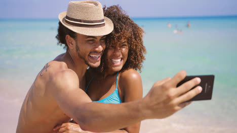 Cheerful-happy-couple-selfies-on-beach