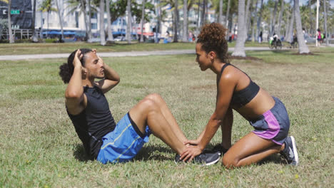 Woman-helping-to-boyfriend-with-abdominal-exercise