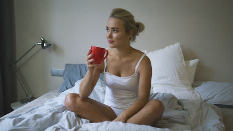 Woman-in-underwear-drinking-on-bed