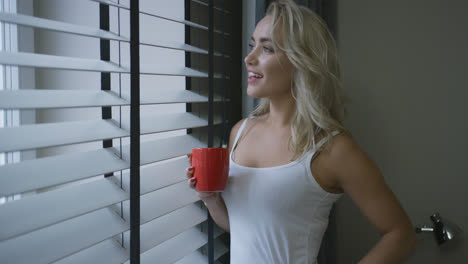 Cheerful-woman-with-mug-looking-out-window