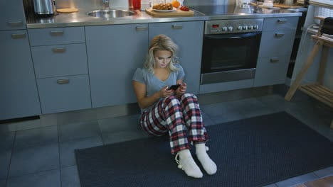 Lovely-woman-browsing-smartphone-on-kitchen-floor