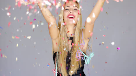 Sexy-blond-girl-blowing-confetti-to-camera-direction