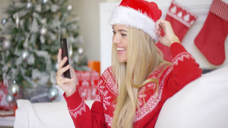 Young-happy-blond-girl-in-Christmas-outfit-using-mobile-phone